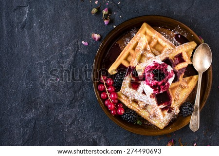 Traditional Belgian waffles with ice cream and berry fruit sauce in the plate,selective focus and blank space