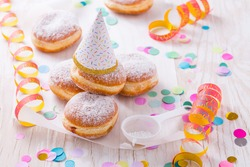 Traditional Berliner with party hat for carnival and party. German Krapfen or donuts with streamers and confetti. Colorful carnival or birthday image