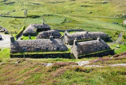 Traditional blackhouses roofed with wooden rafters covered with a thatch of turf with cereal straw (or reed) in Garenin township on the Isle of Lewis in the Outer Hebrides of Scotland, UK