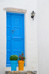 Traditional blue door in small greek village together with colorful flowerpots against white washed cycladic house