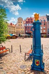 Traditional blue water pump with gryphon head crest from Szczecin city emblem and old town square in background. Gryphon is Stettin emblem since 1360