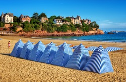 Traditional blue white striped tents on a sand beach in Dinard, Brittany, France