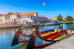 Traditional boats on the canal in Aveiro, Portugal. Colorful Moliceiro boat rides in Aveiro are popular with tourists to enjoy views of the charming canals. Aveiro, Portugal.