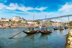 Traditional boats with wine barrels and Douro River in Porto in a beautiful summer day, Portugal