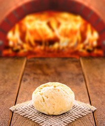 traditional Brazilian cheese bread, with oven in the background. Hot cheese bread served freshly. Mineira food, wood burning stove.