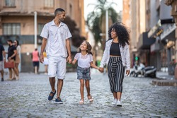 Traditional Brazilian family. Father and mother walking with their daughter.
