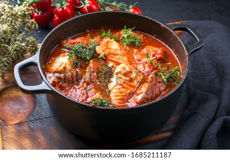 Traditional Brazilian fish stew moqueca baiana with fish filet in tomato sauce as closeup in a modern design cast-iron roasting dish