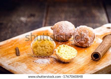 Traditional Brazilian mini fried cake called 'Bolinho de Chuva' open, cut in half, on a rustic wooden kitchen board. Foto stock ©