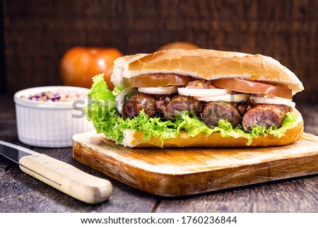 traditional Brazilian sandwich of bread with sausage, tomato, onion and lettuce. Crispy salt bread with roasted or fried sausage. Foto stock ©