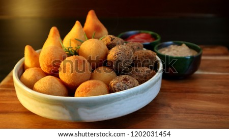 Traditional Brazilian snacks coxinha and quibe on wooden dark background. Selective focus. #1202031454