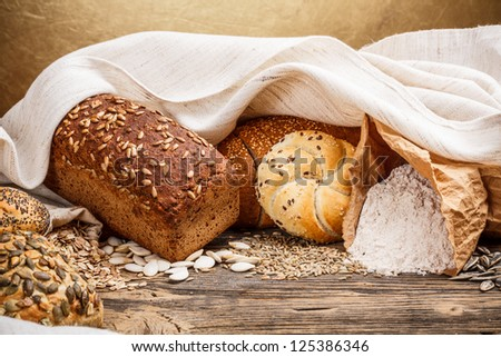 Traditional bread and bun on old wooden table