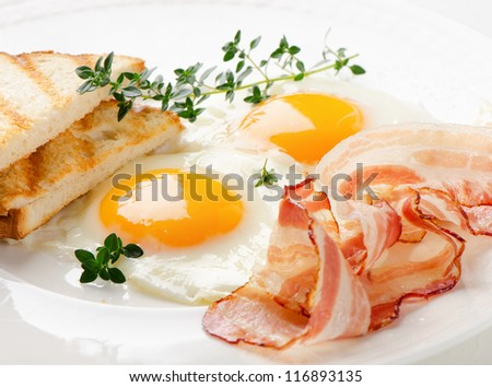 Traditional breakfast -  bacon , fried eggs and toast