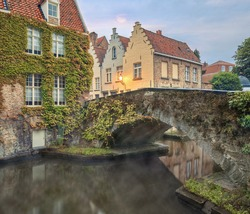 Traditional brickwall architecture of Bruges on water canals with bridges