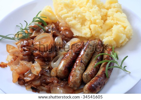 "Traditional British ""bangers and mash"" fried sausages with onions and mashed potatoes."