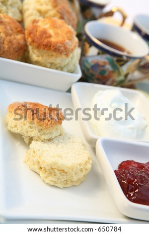 Traditional British cream tea with scones, cream, strawberry jam and tea. An afternoon treat.