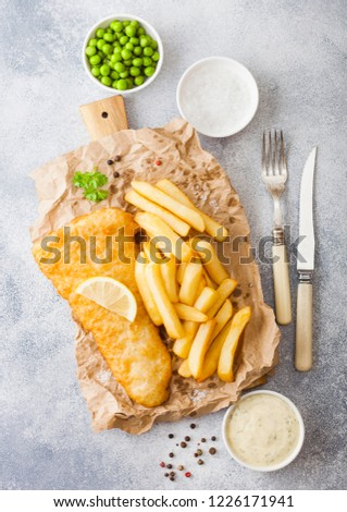 Traditional British Fish and Chips with tartar sauce on chopping board with fork and knife and green peas on white stone table background. Stock photo ©