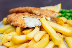 Traditional British Food such as Fish and Chips with green peas served in the Pub or Restaurant