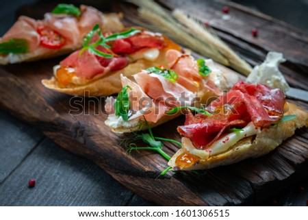 Traditional Bruschetta set with Parma dried ham and prosciutto. Italian antipasti  sandwiches with jamon, cottage cheese, arugula, and sun-dried tomatoes on a rustic wooden Board Stock photo ©