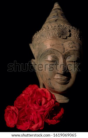 Traditional Buddhist head statue with red roses. Zen Buddhism, mindfulness and love. Face of mindful Buddha in calm meditation. Spiritual enlightenment and tranquility. Black background portrait image