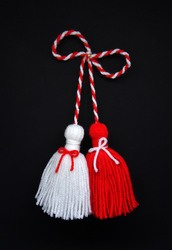 Traditional Bulgarian Martenitsa, red and white tassels. black background