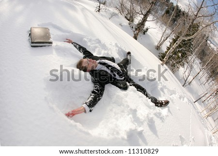 traditional businessman lying in snow making an angel