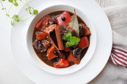 Traditional Byzantine style beef stew with red wine, red pepper, cinnamon, all spices and raisins. In a white plate. Horizontal top view from above Close-up on a white surface table. Copy space.