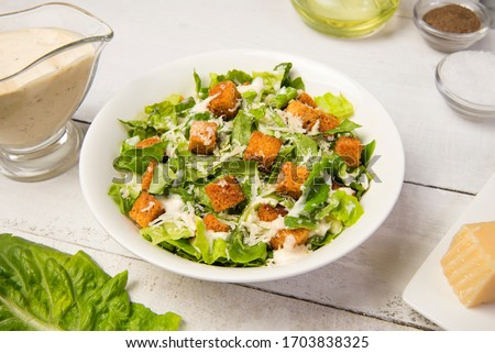 Traditional caesar salad in a white bowl on a old white table with leaves and a sauce boat and parmesan. Selected focus.