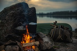 Traditional camping scene, canoe and campfire on a back country lake in the evening