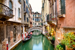 Traditional canal street with gondola in Venice, Italy