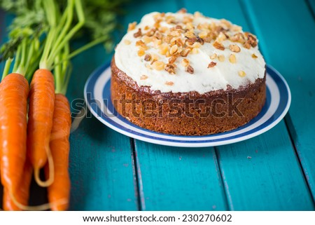 Traditional carrot cake and fresh carrots on table