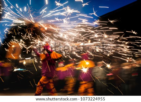 traditional catalan correfocs running in celebration with fireworks and people dressed like demons in barcelona city center, spain