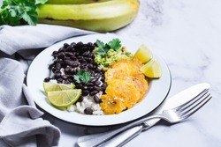 Traditional Central American caribbean cuban colombian food. Rice with black beans, tostones, fried green bananas plantains with guacamole sauce