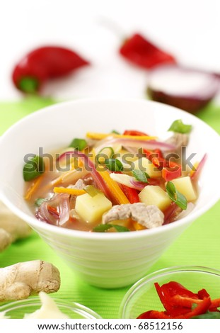 Traditional Chinese chicken soup with potatoes, ginger, paprika and peppers
