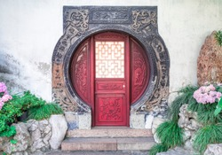 Traditional chinese circular red door with wooden ornaments at Yu Gardens, Shanghai, China