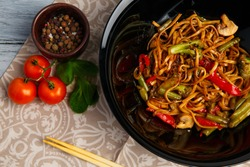Traditional Chinese dish on a round plate, rice noodles, cabbage green cabbage and fried vegetables, red cherry tomatoes.
