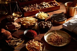 Traditional chinese herbal medicine. Ancient Chinese medicine and herbs on wooden table