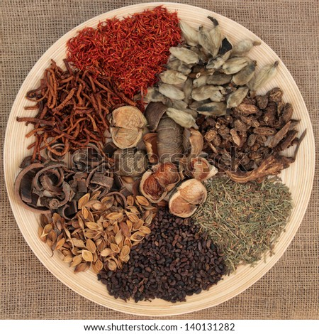 Traditional chinese herbal medicine selection on a wooden bowl over hessian background.