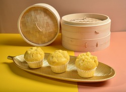traditional chinese yellow cup cake (huat kueh) dessert on gold leaf long plate with dim sum bamboo basket new
