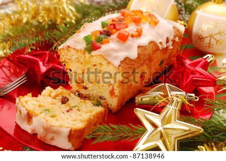 traditional christmas cake  (keks ) with dried fruits,jelly and icing on red plate