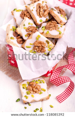 Traditional christmas cookies with walnut and pistachio nuts in a red box with white paper on a wooden board