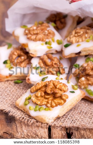 Traditional christmas cookies with walnut and pistachio nuts on a wooden board