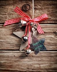 Traditional Christmas decoration with checkered bow, silver bells and star shapes wishing Merry X-mas, hanging on a rustic wooden wall