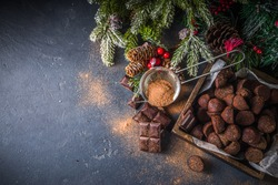 Traditional Christmas dessert, homemade chocolate truffles, with dark chocolate slices, winter spices and christmas tree decor on dark  background. copy space
