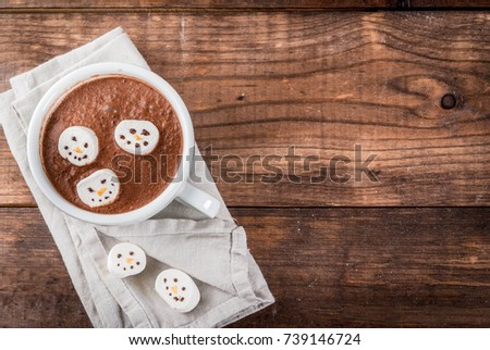 Traditional Christmas drink idea. Hot chocolate mug with marshmallow, decorated in the form of snowmen, On wooden table copy space