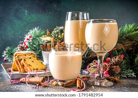 Traditional Christmas egg dairy drink with spices, in different glasses. Eggnog cocktail, Cola de mono, Crème de Vie (Cream of Life) beverage. Dark background with Christmas decor Foto d'archivio ©