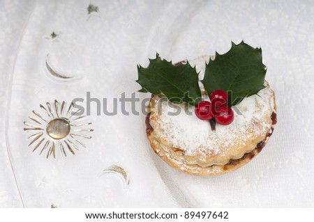 Traditional Christmas English mincepies decorated with icing sugar and holly with berries.  On an attractive glass plate with sun and moon.