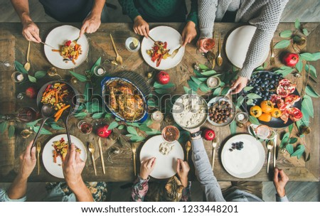 Traditional Christmas, New Year holiday celebration party. Flat-lay of friends or family eating at festive table with turkey or chicken, vegetables, mushroom sauce, fruit, top view #1233448201