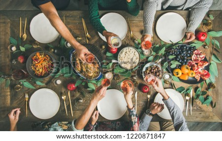 Traditional Christmas, New Year holiday celebration party. Flat-lay of friends or family feasting at festive table with turkey or chicken, roasted vegetables, mushroom sauce and fruit, top view