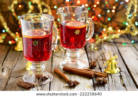 Traditional Christmas punch with spices such as cinnamon and star anise in a glass cups decorated with golden stars