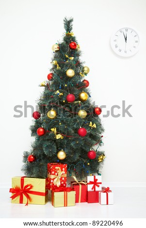 Traditional Christmas tree with baubles and gifts on white